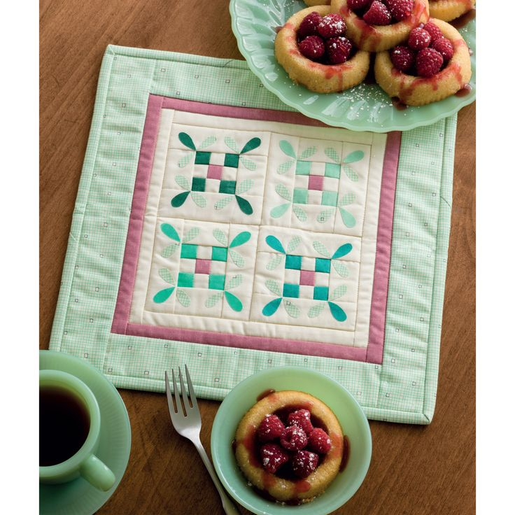 The blocks in this charming mini quilt by Sandy Gervais combine patchwork and applique to resemble little bees buzzing around a blossom.