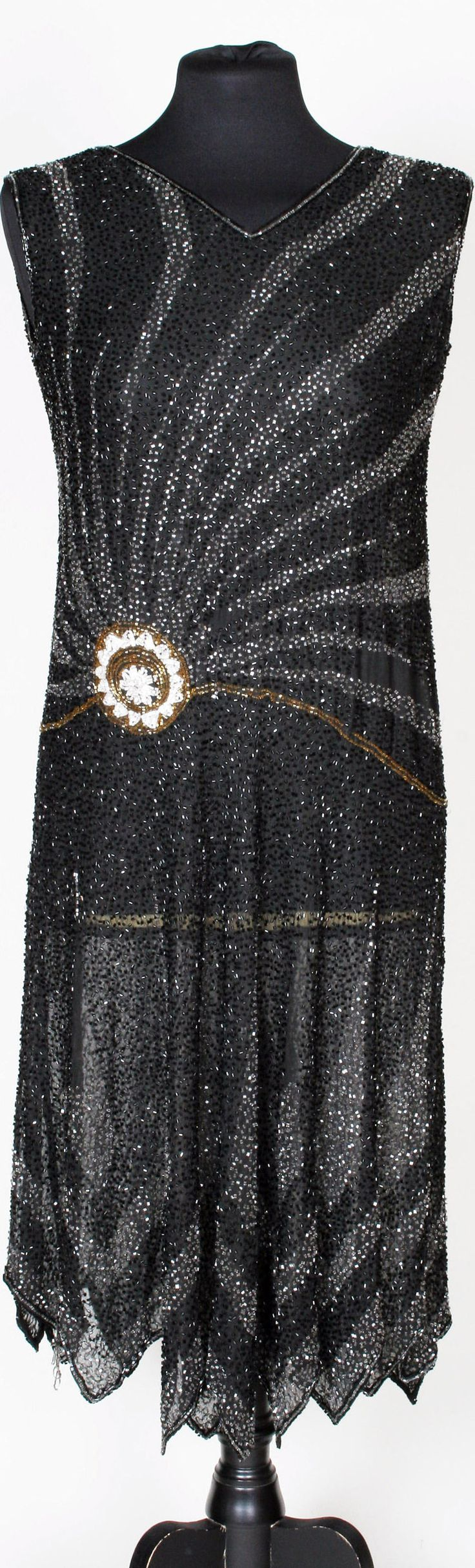 A 1920s black beaded flapper dress with a sun ray design stemming from the waist with a central circular decoration of gold and white beads. Bonhams
