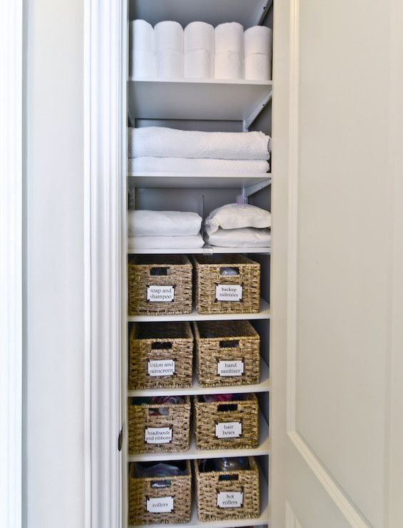 Well organized closet features rolls of toilet paper on top shelf, freshly washed towels and linens on second and third shelves shelves and the rest of the shelves are filled with woven baskets with tags filled with bath accessories.
