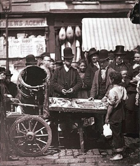 "Joseph Carney, a street vendor or ""costermonger"", sells fresh herring from a barrow in a street market near Seven Dials. The character on the right holding a white pitcher was known locally as ""Little Mic-Mac Gosling"", as despite being 17 years-old, he was only three feet 10 inches high.   Picture: 'Dickens's Victorian London' by Alex Werner and Tony Williams."