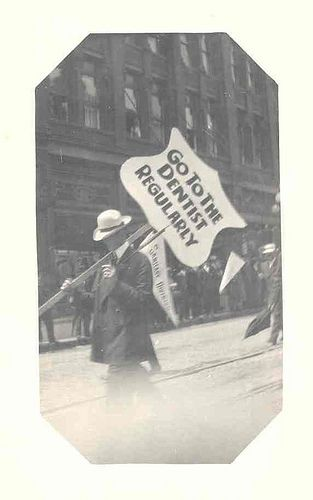 """""""Go to the Dentist Regularly"""" sign in parade, circa 1911"""