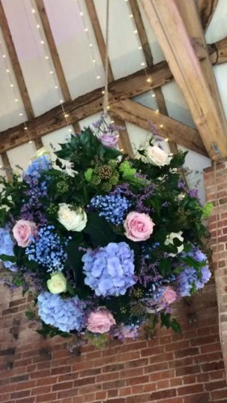 hanging baskets of flowers hanging from the pulley's in Shustoke Farm Barn. #flowerdisplay #floralspheres #floralbaskets #pulleydisplays #pulleyflowers #shustokefarmbarn #pennyjohnsonflowers #impressivedisplays #largefloraldisplays #floralball
