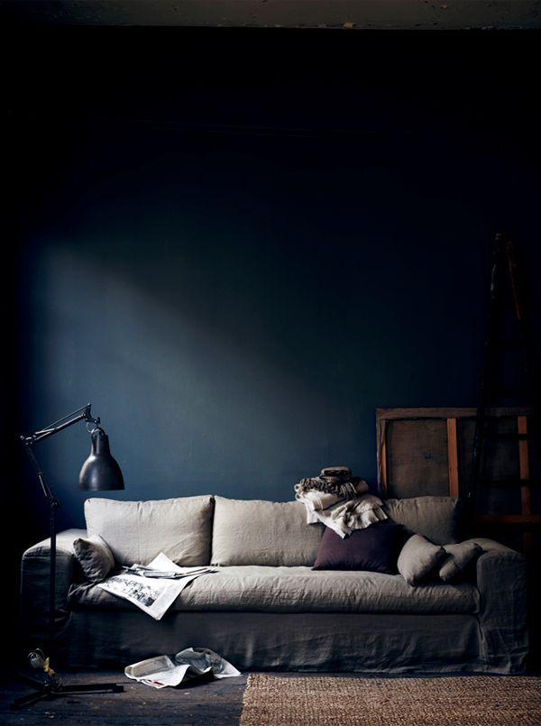 Dramatiskt vardagsrum med djupt blå väggar