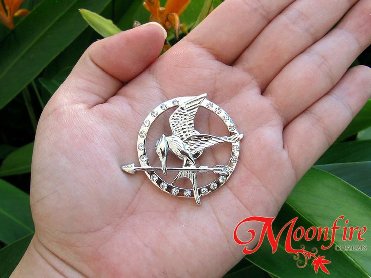 This Mockingjay pin is the replica of the pin Katniss keeps close to her. It is encrusted with CZ gems all around the rim. The silver/gold plated pin measures 3.5 cm in diameter. Available in silver a