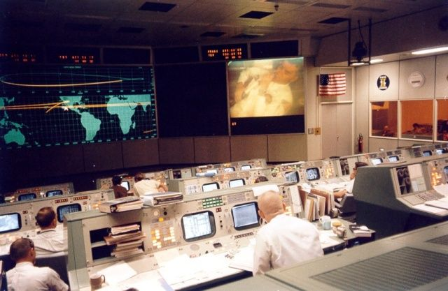 Flight Director Gene Kranz watches Fred Haise on the big right-hand Eidophor TV monitor shortly before the explosion.