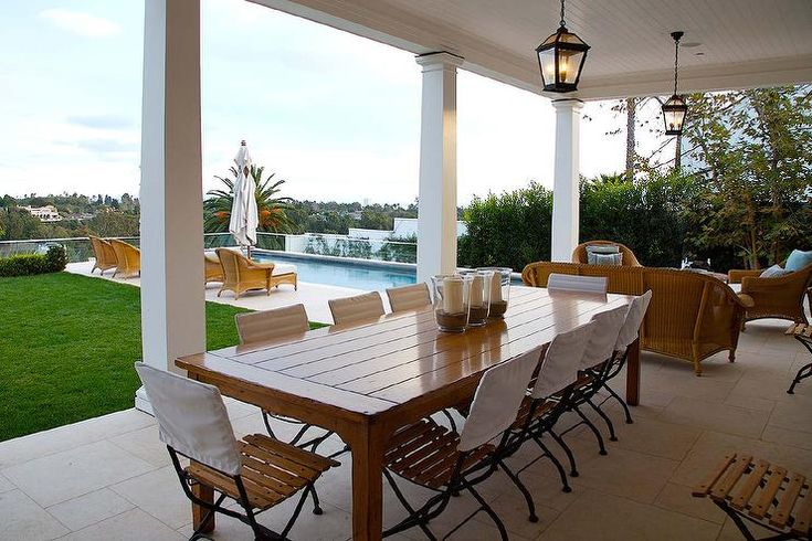 Rectangular patio dining table seats 10 slatted seat dining chairs finished with a square white fabric back and is lit by a bronze carriage lantern hung…