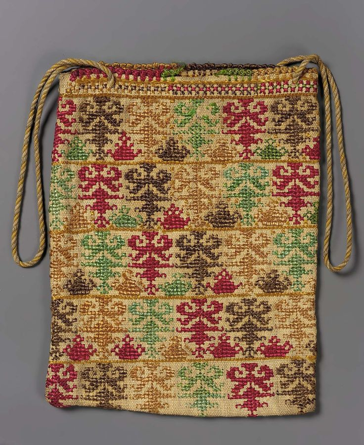 Rectangular bag. Coarse tabby-woven linen, folded and stitched to form narrow, deep bag. Yellow, cream and beige cord as handle. Faces of bag show conventional plants or trees embroidered with coarse polychrome silks in cross and stem stitches. Cotton browned; a few stains.
