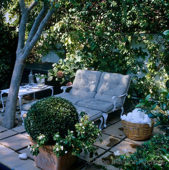 A pair of upholstered wrought-iron garden chaises in the shade of a convenient tree on an impromptu terrace