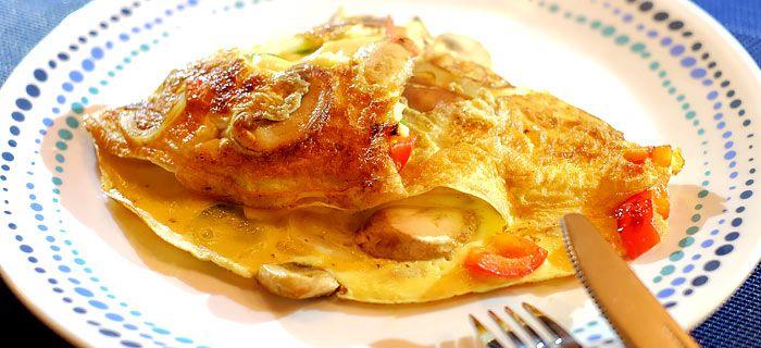 Deze omelet met champignons, ui, paprika, komkommer en cheddar is heerlijk op een dikke plak geroosterd boerenbrood. Hier vind je het makkelijke recept.