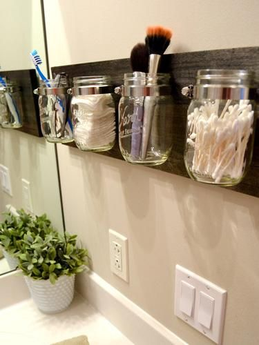Mason jars attached to wooden board make bathroom storage look farmhouse-chic.
