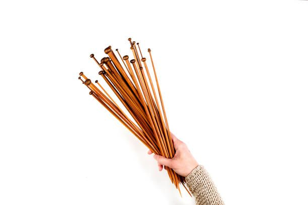 woman hand holding a lot wooden knitting needles on white background