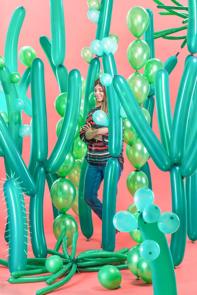 Sarah Illenberger self portrait for Architectural Digest Magazine in the middle of a green cacti garden made of metallic balloons with a bold pink background. Photography: Christian Hagemann #cactus #balloon #pink #green - Carefully selected by GORGONIA www.gorgonia.it