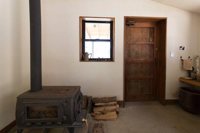 玄関がコンクリートの土間になっていて、そこに薪ストーブが置かれている。