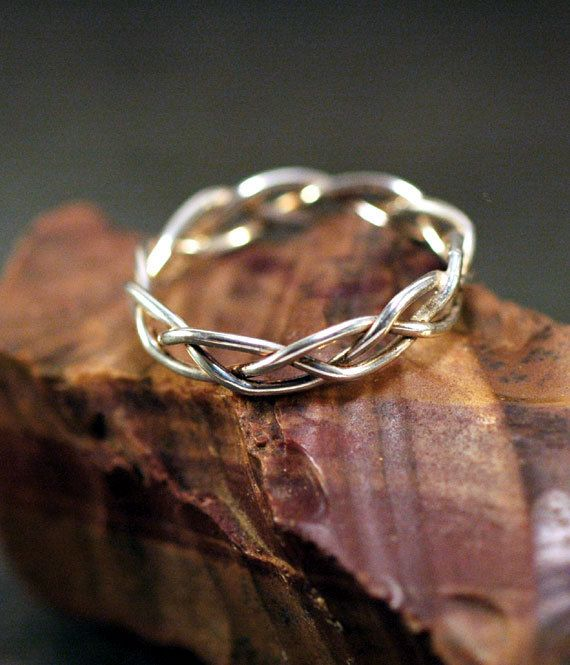 Something like this perhaps...but with leaves holding the diamond in place.  This way the braid would look like vines.  Not sure how comfortable it would be though...  Unique wedding band. Looks durable and only $40