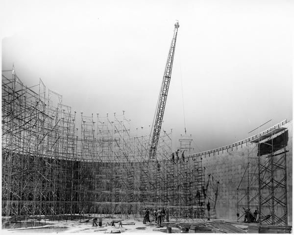 View of the erection of a tall network of scaffolding around the interior perimeter of a partially built giant water tank. Commissioned by the Patent Scaffolding Company. Location tentatively identified as Claiborne and Leonidas Streets.