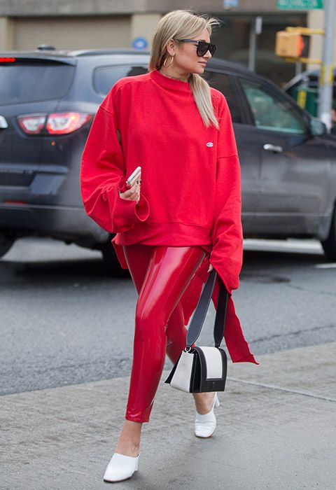 A NYFW attendee wearing skintight red PVC trousers and a matching oversized sweatshirt, complete with white mules and a clutch | ASOS Fashion & Beauty Feed