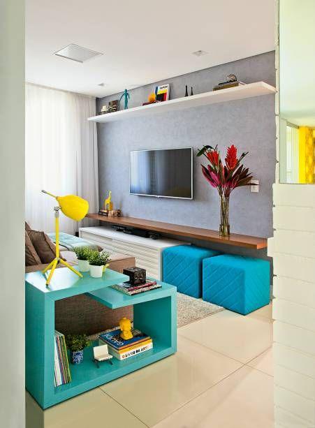 O moderno efeito de concreto na parede da TV foi conquistado com papel de parede que imita o material. Acendem a decoração os pufes turquesa Morás, de 45 x 45 x 45 cm (Oppa). Projeto da arquiteta Bruna Carra.