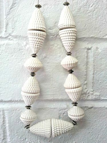 Corrugated-paper-beads - rolled white, corrugated card stock, use fingers to shape the discs into cones, coat each with white nail polish, and  spray the whole piece with several light coats of lacquer.