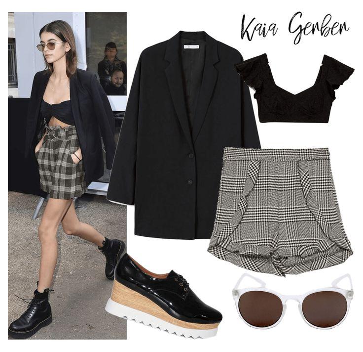 Kaia Gerber En Tartán  Casual pero muy chic con un short en tartán de talla alta, un crop top y un blazer negro.