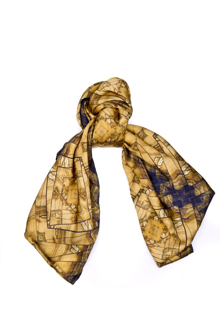Lumière de Louvre  - Long Scarf.  This stunning design captures the architectural magnificence of the Louvre in Paris, France. It transforms the regular perception of the Louvre kaleidoscope of elegance. Its simple use of color and shape makes this piece a ravishing finishing piece for any look.