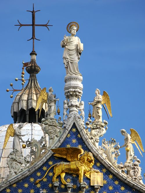 St Mark's Cathedral, Venice. Detail of the rooftop showing Venice patron apostle St. Mark with angels. Underneath is a winged lion, the mascot of Venice. It is the most famous of the city's churches and one of the best known examples of Byzantine architecture. It lies at the eastern end of the Piazza San Marco, adjacent and connected to the Doge's Palace.