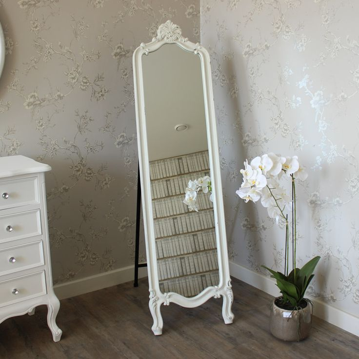 Ornate White Painted Wooden Cheval Mirror A stunning floor length mirror with ornate detailing on the top and legs Perfect for adding French style elegance to your bedroom Made from wood and painted in a white distressed finish With black metal stand on the back