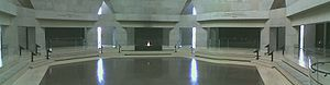 Panoramic view of the Hall of Remembrance. Hexagonal room with red-tile floor, limestone walls, and black panels. Eternal flame in foreground supported by a black box containing ashes from European Concentration Camps.  United States Holocaust Memorial Museum