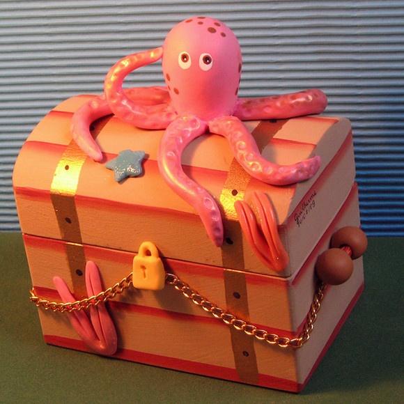 Baú com o polvo em biscuit e mdf. Mínimo de 20 peças.Temos vários personagens do Fundo do mar.Fornecemos surtidos conforme o cliente escolher.Temos outros tamanhos maiores de baú.Ligar ou enviar e-mail para saber preço dos correios e detalhes personalizados.Tel 21-26053020 , fontebonsai@yahoo.com.br Para ver outros personagens entre em: http://www.noivinho.com.br/fundo-do-mar-polvo.htm R$16,00