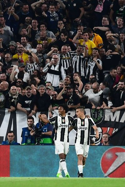 Juventus' forward from Argentina Paulo Dybala (R) celebrates with teammate Juventus' forward from Colombia Juan Cuadrado after scoring during the UEFA Champions League quarter final first leg football match Juventus vs Barcelona, on April 11, 2017 at the Juventus stadium in Turin.  / AFP PHOTO / MIGUEL MEDINA