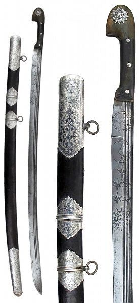 Ottoman shashka, probably Circassian craftsmanship, horn grips with large nielloed silver sun, early 18th c blade with 3 narrow fullers etched with sun, moon and stars and an arm gripping a saber springing from a cloud, talismanic inscriptions, scabbard with 4 large nielloed silver mounts with flowering vine motifs, the obverse locket with Ottoman Sultan's tughra, reverse inscribed: Quli Khan 1309 (1891 c.e.), possibly Naja Quli Khan, the Iranian Consul General to the Ottoman Empire, 103.5…