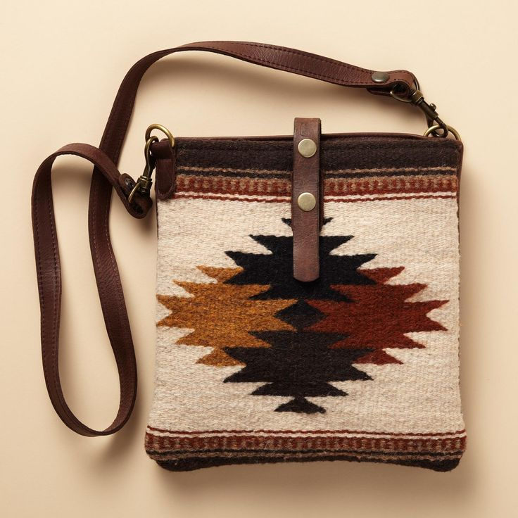 "TRIBAL CROSSBODY BAG -- Compact and comfortable to wear, this American-made bag combines soft pebbled leather with wool tapestry woven in a Navajo pattern. Distressed leather strap with adjustable snap closure, cotton-lined interior with one pocket. Made in USA. 10-1/2""W x 1""D x 10-1/2""H."