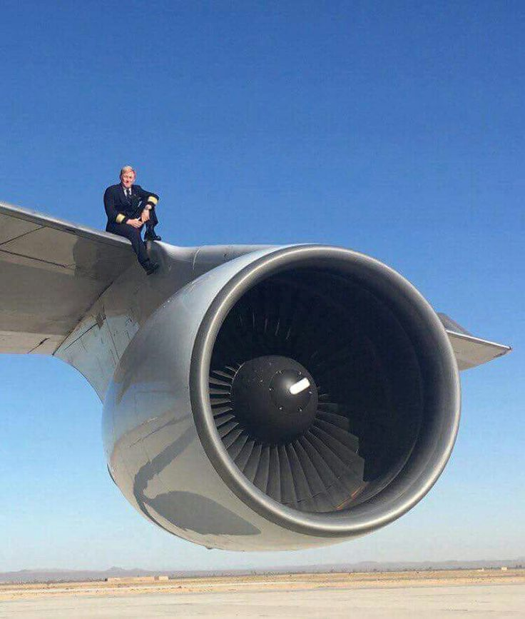 United Airlines captain sitting on the wing of a company Boeing 747-422 directly above one of the 4 Pratt and Whitney PW-4000 turbofans
