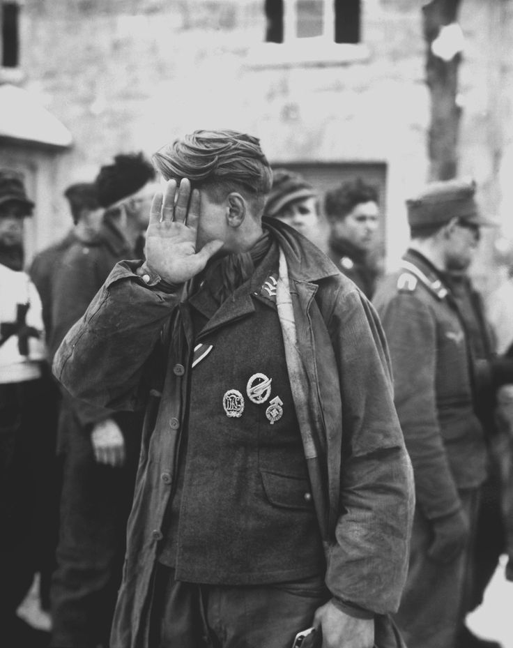 ww2 • german pow covering his face from a us army signal photographer. belgium 1945