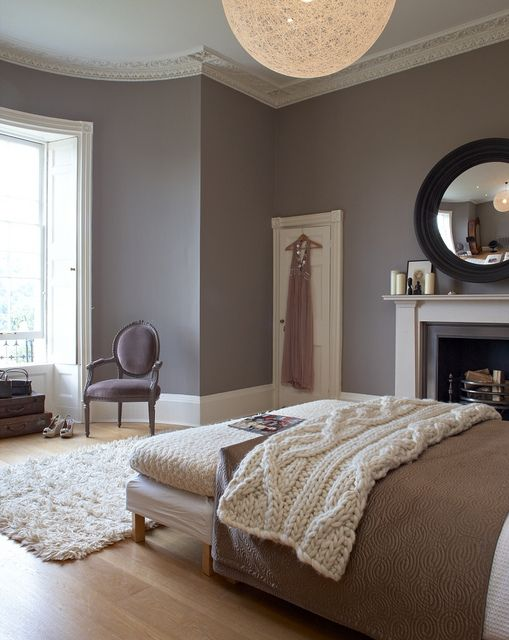 Cozy contemporary bedroom with warm colors. Love the round mirror above the fireplace.