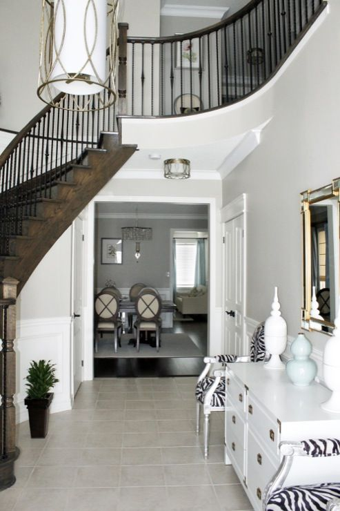 Foyer, wainscoting, Benjamin Moore Revere Pewter paint, Troy Sausalito lighting, curved staircase, wrought iron spindles, campaign foyer dresser, silver-leaf zebra Louis chairs, geometric mirror, white porcelain urns with finials    Benjamin Moore Revere Pewter     view 42 more ...