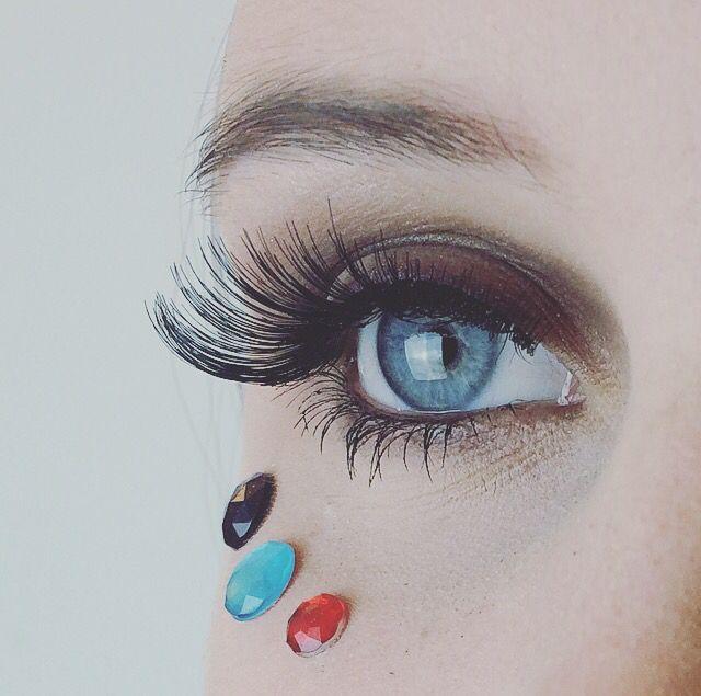 Makeup av mig, närbild. Jag använde mig utav ett par snygga långa och relativt täta fransar från märket ARDELL. Jag satte fast tre plast diamanter (med ögonfrans-lim) under modellens ögon för att få en mer festlig look.  Jag valde den blå diamanten för att framhäva hennes vackra blåa ögonfärg.  Jag tog den röda diamanten för att få fram och matcha den röda färgen jag använde på modellens läppar. Slutligen valde jag en lila sten, för att enkelt matcha den lila eyeliner jag placerat. (Svårt…