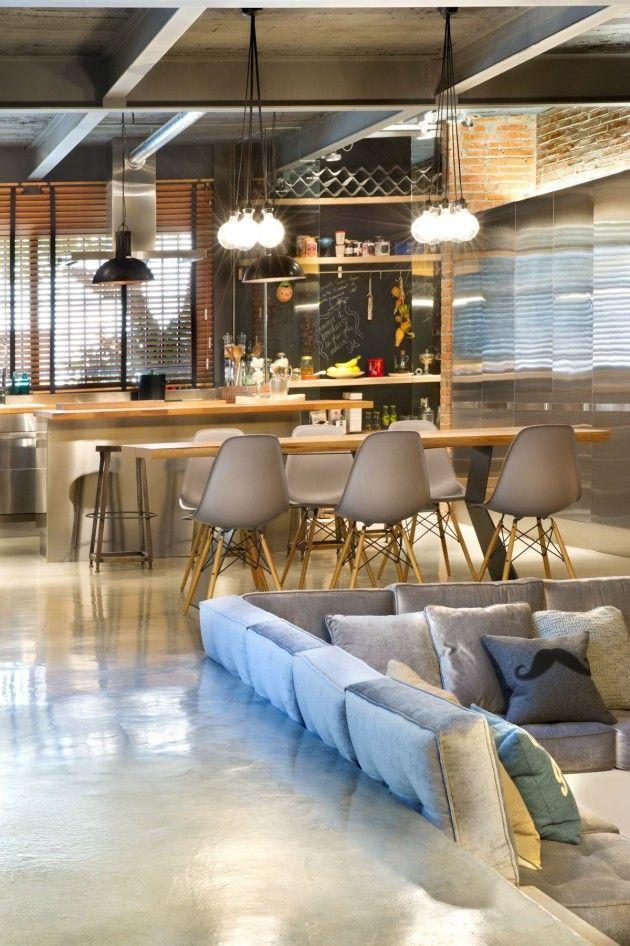 Cozinha e sala integradas em loft em Terrassa, Espanha, com detalhes contemporâneos e industriais como o teto sem forro, luminárias pendentes mais simples, armários com porta de metal e o piso em cimento queimado.