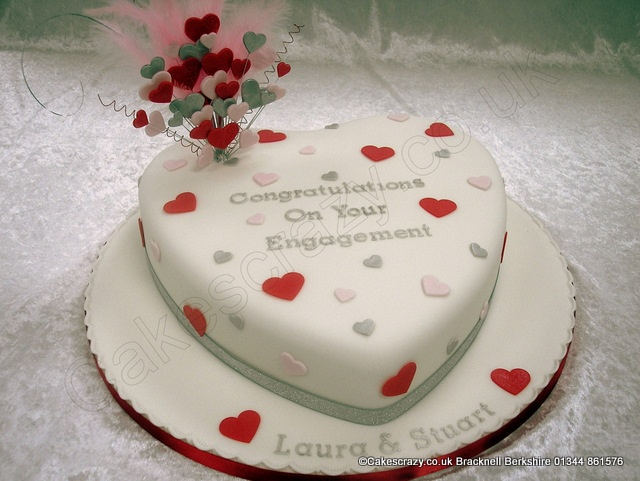 Large white heart shaped engagement cake. The cake is decorated with simple red, pink and silver hearts, and topped with a wired explosive heart and feathered cake topper. Finished with silver glitter and red satin ribbons