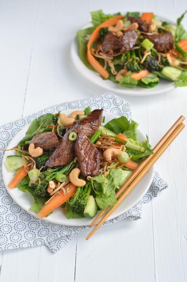 Oosterse salade met biefstuk - 200 gr Romaine sla, 3 wortelen, 1 stukje komkommer van 10 cm, 200 gr bimi, 100 gr taugé, 2 lente uitjes, 4 biefstukken, 2 el + 2 el hoisinsaus, Handje cashewnoten, Peper en zout, Olijfolie - Snij de biefstukken in repen van ongeveer 1 cm dik. Breng op smaak met peper en zout, verhit olijfolie in een koekenpan, voeg de biefstuk toe en bak ze op een hoog vuur in ongeveer 2 tot 3 min rondom aan. Voeg 2 el van de hoisinsaus toe en bakt dit mee. Haal de…