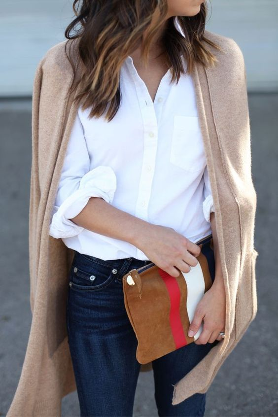 Simple classic style. White button up, dark blue jeans, beige long cardigan. Beautiful camel clutch with stripes.