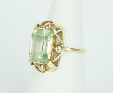 Een 14 krt. geelgouden ring met open sierrand en bezet met een rechthoekige facet geslepen groene amethist, jaren '20/30, maat 16.75.