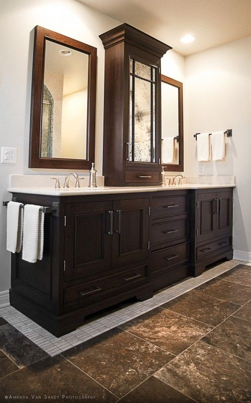 Double Vanity With Storage Tower Cabinet In The Middle And Towel Bar On The Side Of Base Cabinet