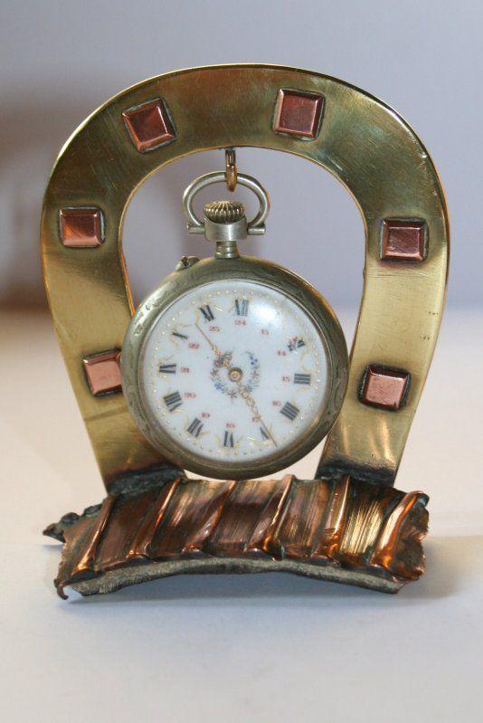 Porte-montre réalisé en forme de fer à cheval en laiton, clous en cuivre soudé sur un morceau de ceinture d'obus.  Haut 10 cm base de 8 cm.