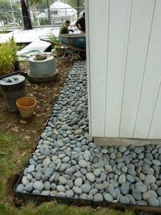 A rock maintenance strip around the house ... catches splashes, keeps walls clean and minimizes pests. Put your foundation plantings in front of the strip.
