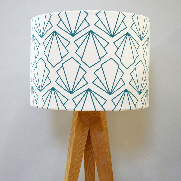 A beautifully handmade lampshade featuring geometric motifs in  turquoise.This lampshade is made with our screen printed cotton fabric,  and bonded to a fire retardant PVC backing with taped edges.All lampshades  are handmade in Brighton.  Each lampshade is handmade and can be used either as a ceiling pendant or  for a lamp base.  20cm H x 20cm D / £45  22cm H x 30cm D / £60  24cm H x 40cm D / £75  UK Postage only / £6  Joanna Corney creates architecturally inspired patterns for the…