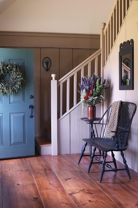 FARMHOUSE – INTERIOR – vintage early american farmhouse showcases raised panel walls, barn wood floor, exposed beamed ceiling, and a simple style for moulding and trim, like in this farmhouse foyer.