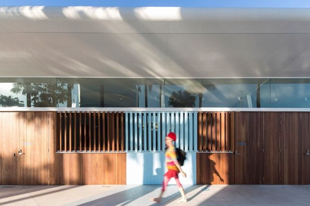 The timber wall, painted in section, is fitted with glass, sliding and fixed panels. Love the shot of aqua blue and the swimmer in red and yellow creates the perfect accent.