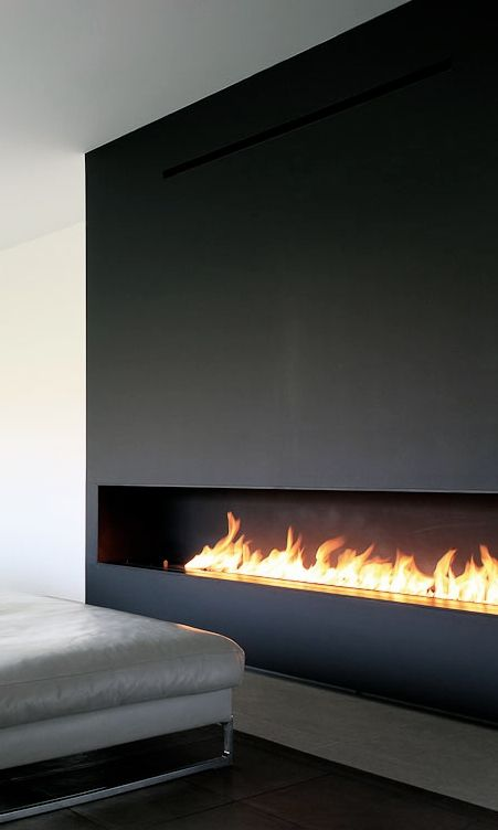 Long, horizontal fireplace in dark wood. Architect unknown.
