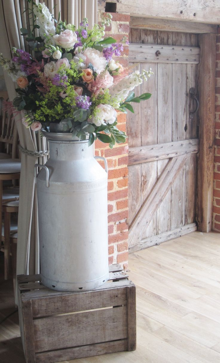 Milk churn of pale pink peony, vuvuzela roses, peach lisianthus, cream spring roses, pale pink stock, lilac freesia, white delphinium, lavender and ivy - Bury Court Barn