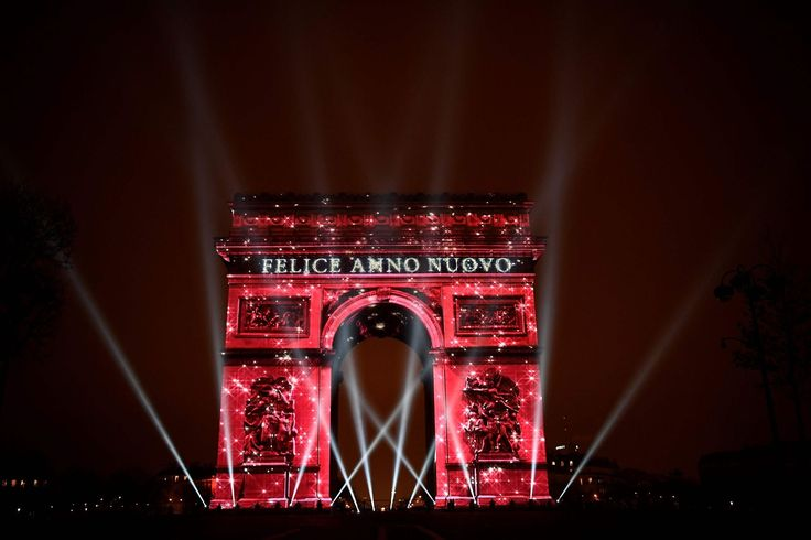 The Arc de Triomphe monument is illuminated by a laser and 3D mapping display reading Happy New Year in Italian as part of New Year celebrations on January 1, 2017 in Paris.